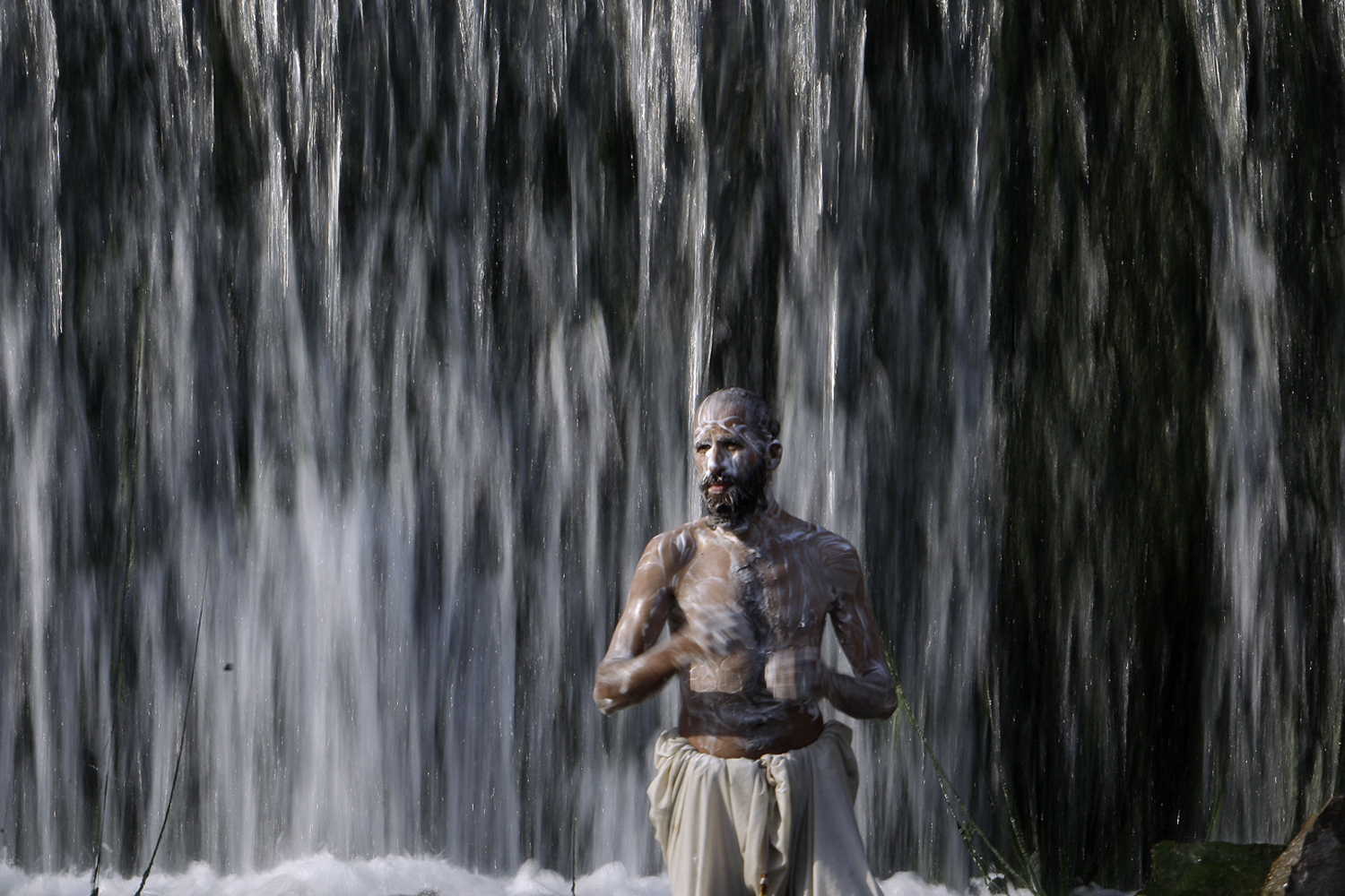 September 28, 2011. A Pakistani man showers in a watercourse in Islamabad, Pakistan.