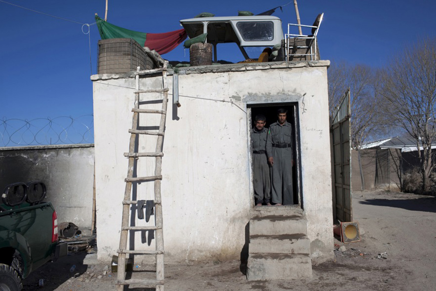 Two Afghan National Police stand at an entry guard post at the district center in Qarabagh, Afghanistan located in Ghazni province. March, 2009