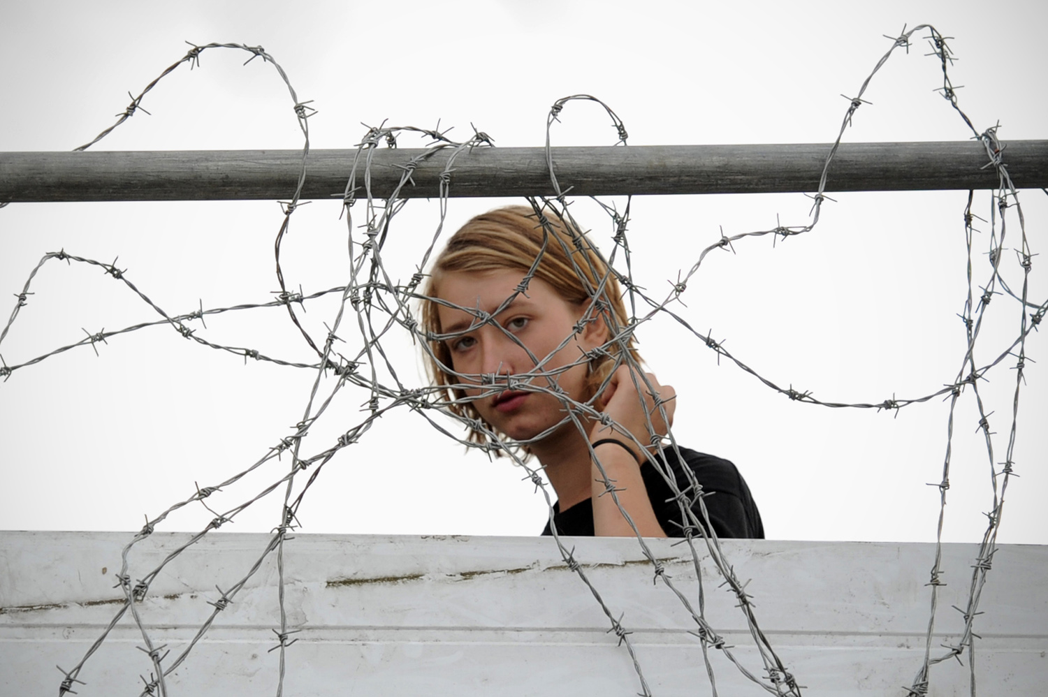 September 26, 2011. An activist looks through barbed wire at the traveler settlement at Dale Farm near Basildon, in south-east England, as resident Kathleen McCarthy addresses the press. Residents battling eviction from Britain's biggest illegal travelers' site won yet another temporary reprieve as a judge granted them an extension on their injunction. Bailiffs acting for the Basildon Council local authority had been set to evict the Irish travelers, but a series of last-ditch legal moves have so far prevented the site being cleared.