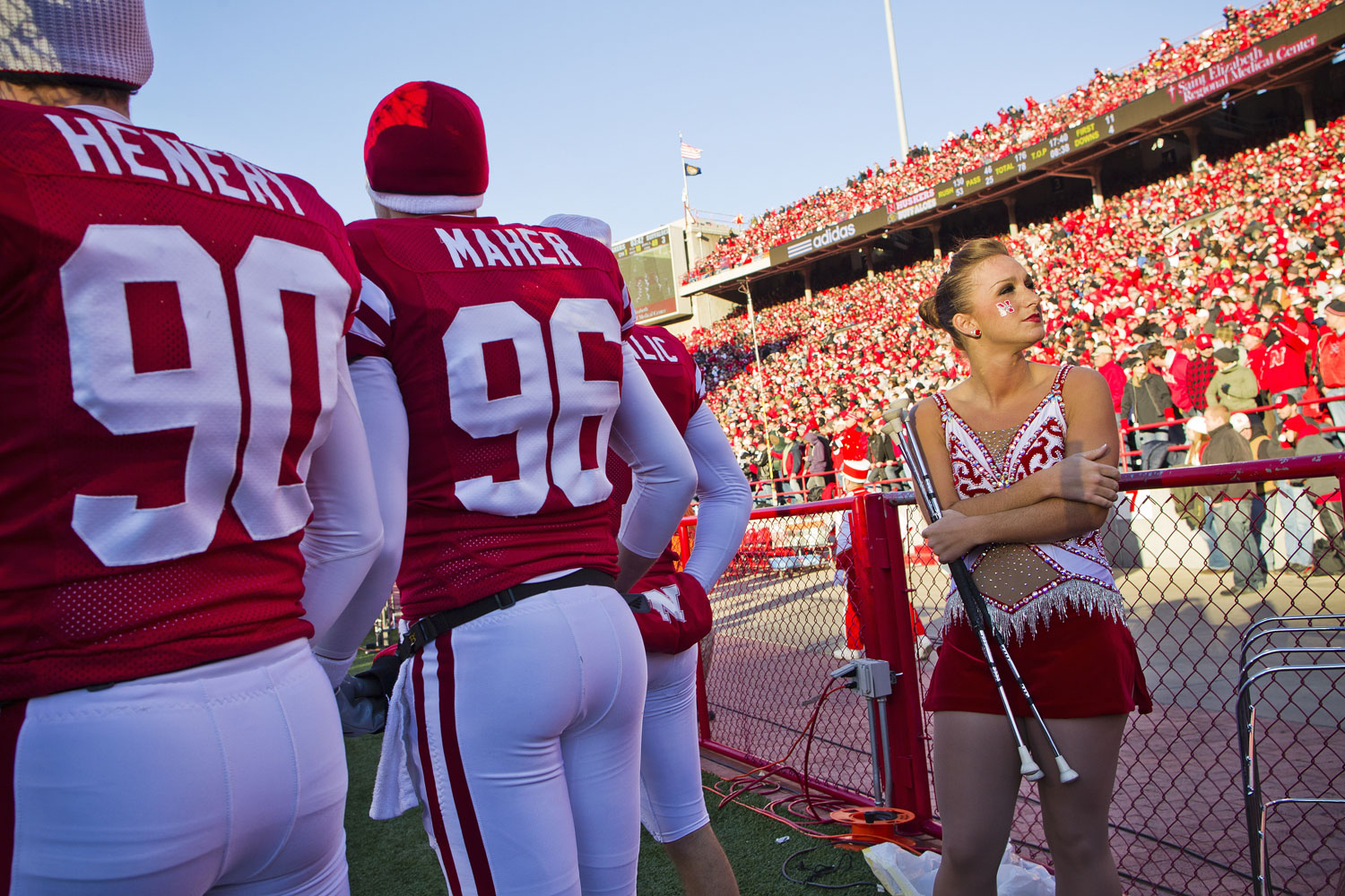 Nebraska's baton twirler Rachel Foehlinger seeks warmth from a heater on the sidelines next to kickers Alex Henery and Brett Maher during a November 2010 game against Colorado.