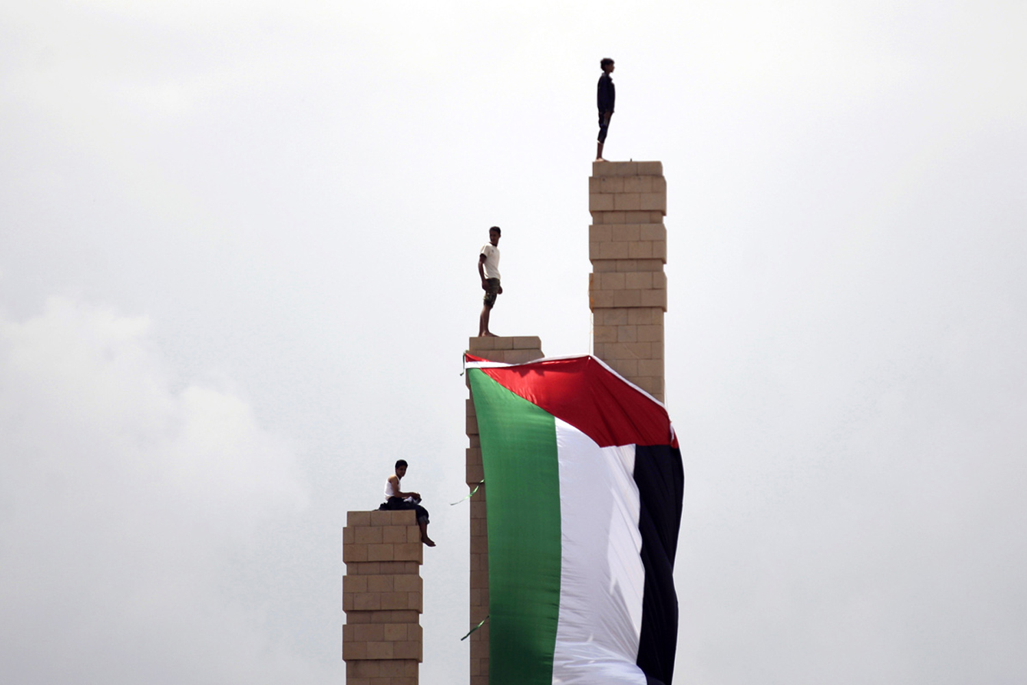 September 23, 2011. Supporters of Yemen's President Ali Abduallah Saleh gather at the Monument of the Unknown Soldier where a Palestinian flag hangs during a rally celebrating his return to Sanaa, Yemen. President Ali Abdullah Saleh made a surprise return to Yemen after more than three months of medical treatment in Saudi Arabia in a move certain to further inflame battles between forces loyal to him and his opponents that have turned the capital into a war zone.