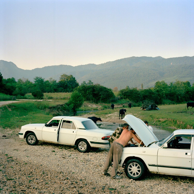 Zaza Katalandze and Tamas Jivanja stop to fix Zaza's car after driving through a small river in Ocumi, Abkhazia.