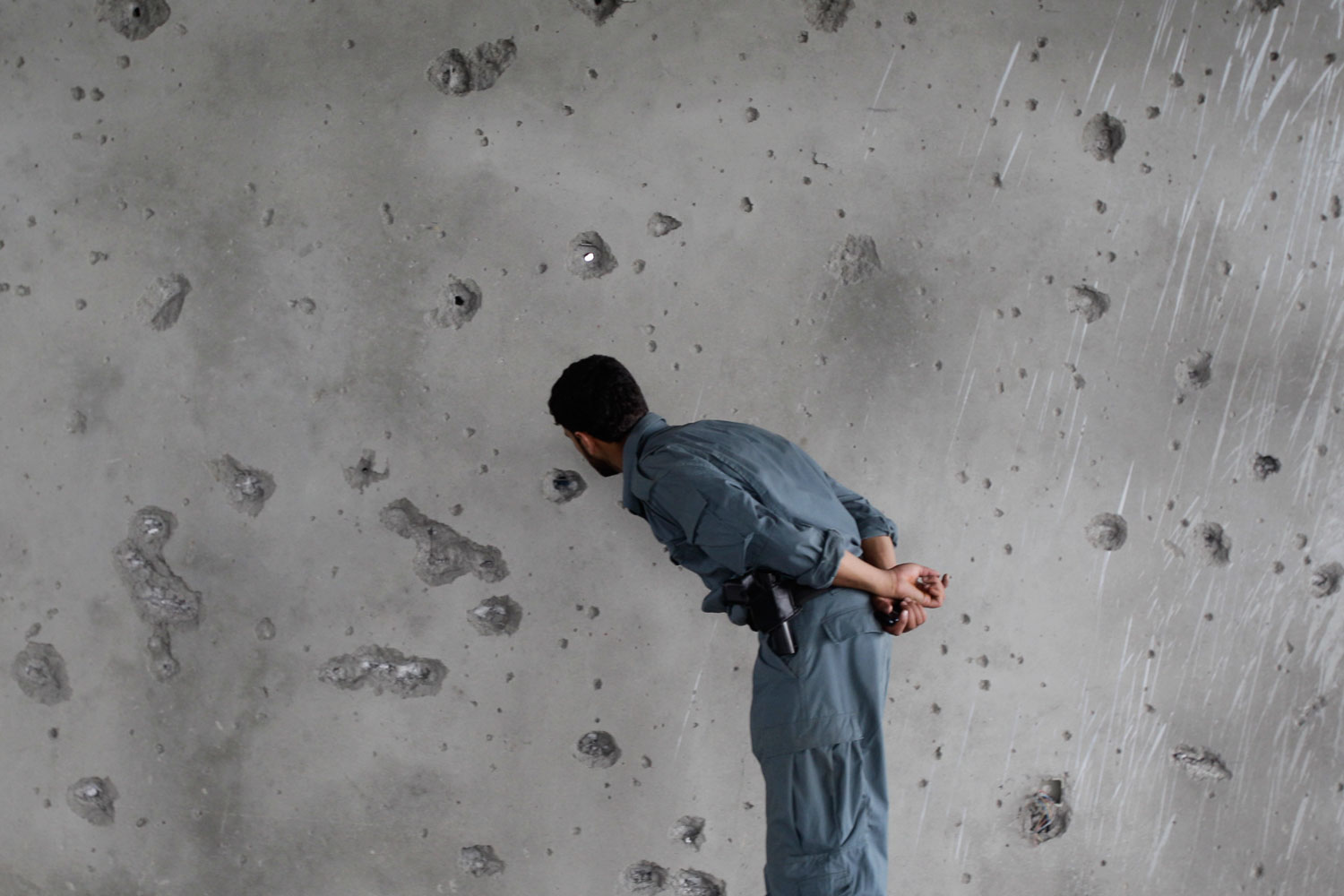 September 14, 2011. An Afghan policeman checks a shattered wall as he visits a building which was occupied by Taliban militants in Kabul, Afghanistan. A 20-hour insurgent attack in the heart of Kabul ended after a final volley of helicopter gunfire. Afghan police ferreted out and killed the last few assailants who had taken over a half-built, downtown building, to fire on the nearby U.S. Embassy and NATO compounds.