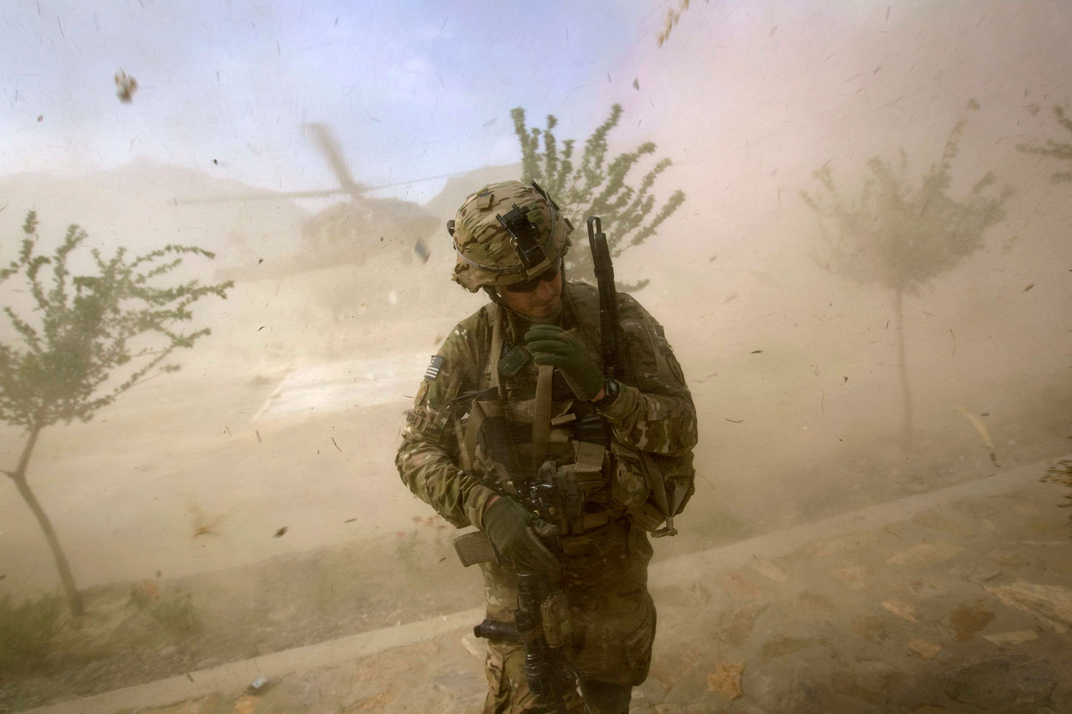 September 15, 2011. 2nd Lt. Andrew Ferrara, 23, of Torrance, Calif., with the U.S. Army's Bravo Company of the 25th Infantry Division, 3rd Brigade Combat Team, 2nd Battalion 27th Infantry Regiment, based in Schofield Barracks, Hawaii, turns from the rotor wash of a landing Blackhawk helicopter during a mission for a key leader engagement at the Shigal district center in Kunar province, Afghanistan.