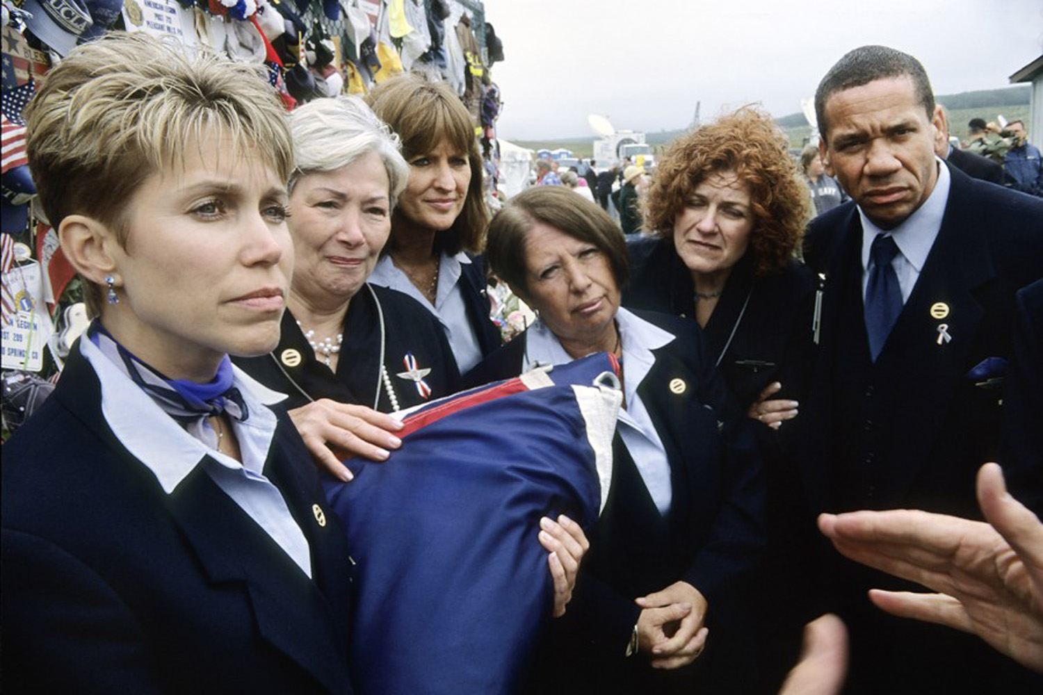 United Airlines flight attendants who sometimes flew on the flight 93 route, accept a flag in honor of the flight attendants lost on 9/11.                               They are standing next to the temporary memorial near the crash site.