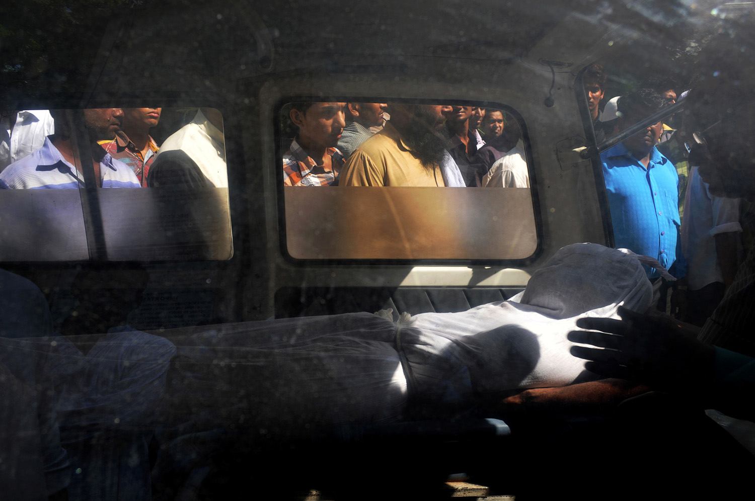 September 28, 2011. The body of a victim of a building collapse lies inside an ambulance outside a mortuary in New Delhi, India. Broken beams and mounds of clay lay in heaps where a three-story residential building collapsed in the Indian capital, killing at least seven people and highlighting the dangerous housing conditions among the city's poor.