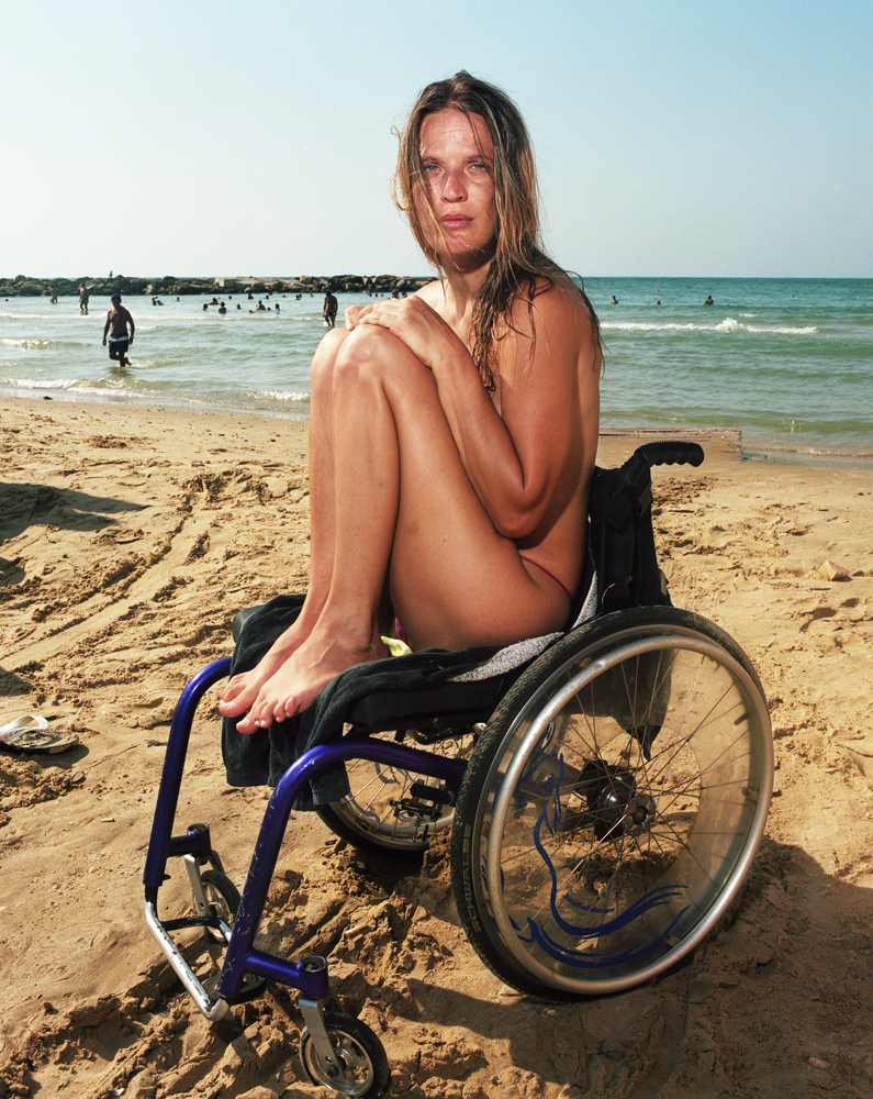 In the decade that Gillian Laub has been photographing in Israel, the Tel Aviv beach remains her favorite place of escape. Among the eclectic group of beach goers is Oxana, 35, who emigrated from the Ukraine as a teenager. She survived a suicide bombing in 2004, but became paralyzed two years later in a roller-blading accident. Her son regularly takes her to a spot on the beach that has a special ramp for handicap access.