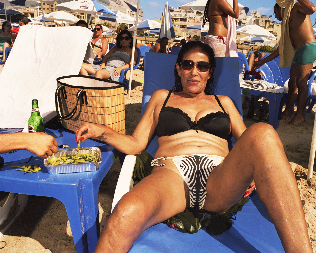 Malka sits with a snack of edamame on the beach.