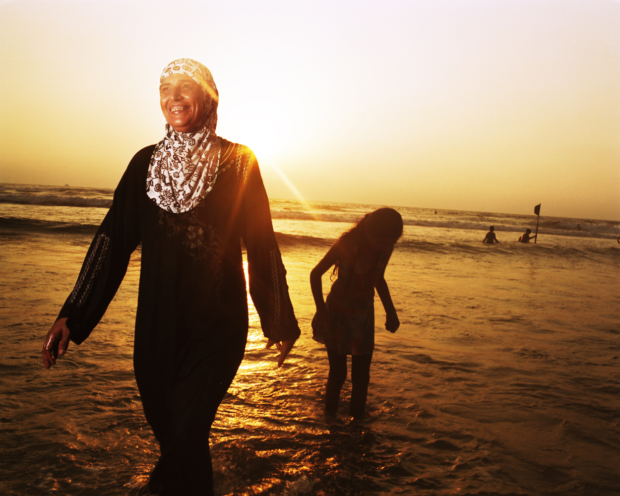 Fatima brings her children to the beach at sunset.