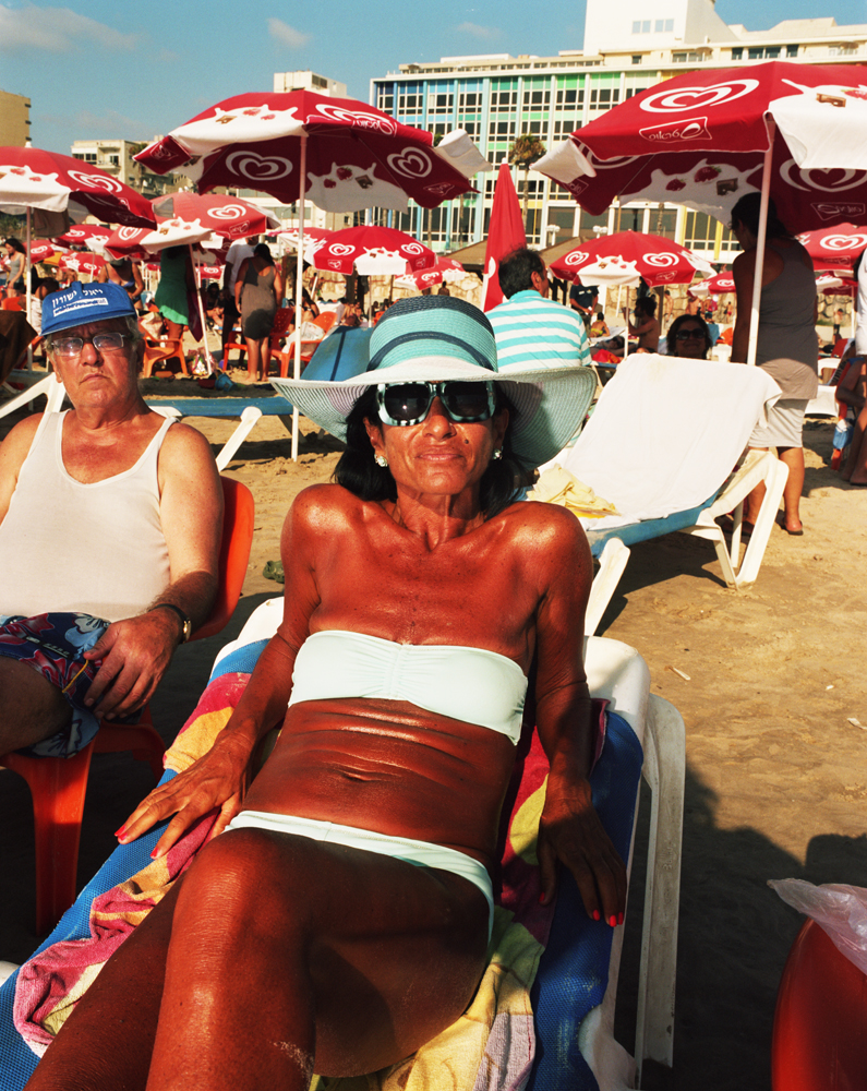 Ruth sits at the same spot on the beach every day. Always carefully color-coordinating her hat, sunglasses, bag and bathing suit, the beach serves as her fashion runway.