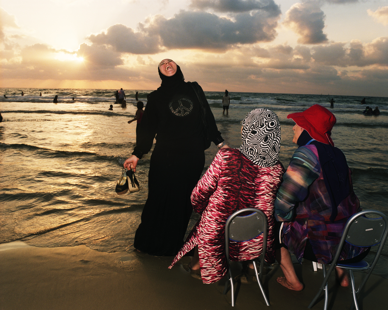 Women watch the sunset while standing at the southernmost edge of the beach near Jaffa.