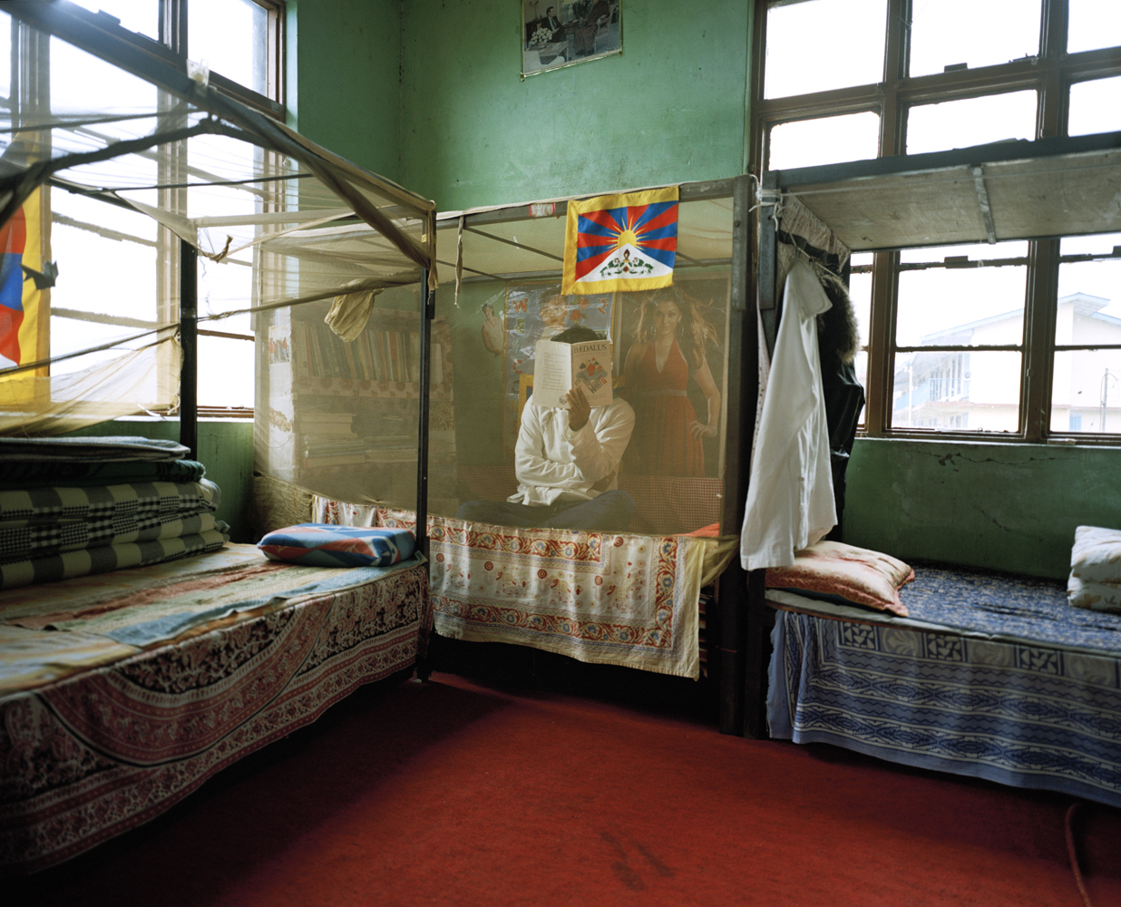 A student conceals his face on his bed inside the men's dormitory at the Tibetan Transit School.