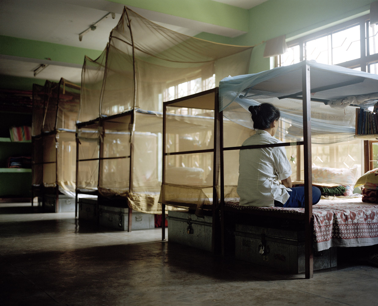 A woman sits on her bed inside the women's dormitory at the Tibetan Transit School.
