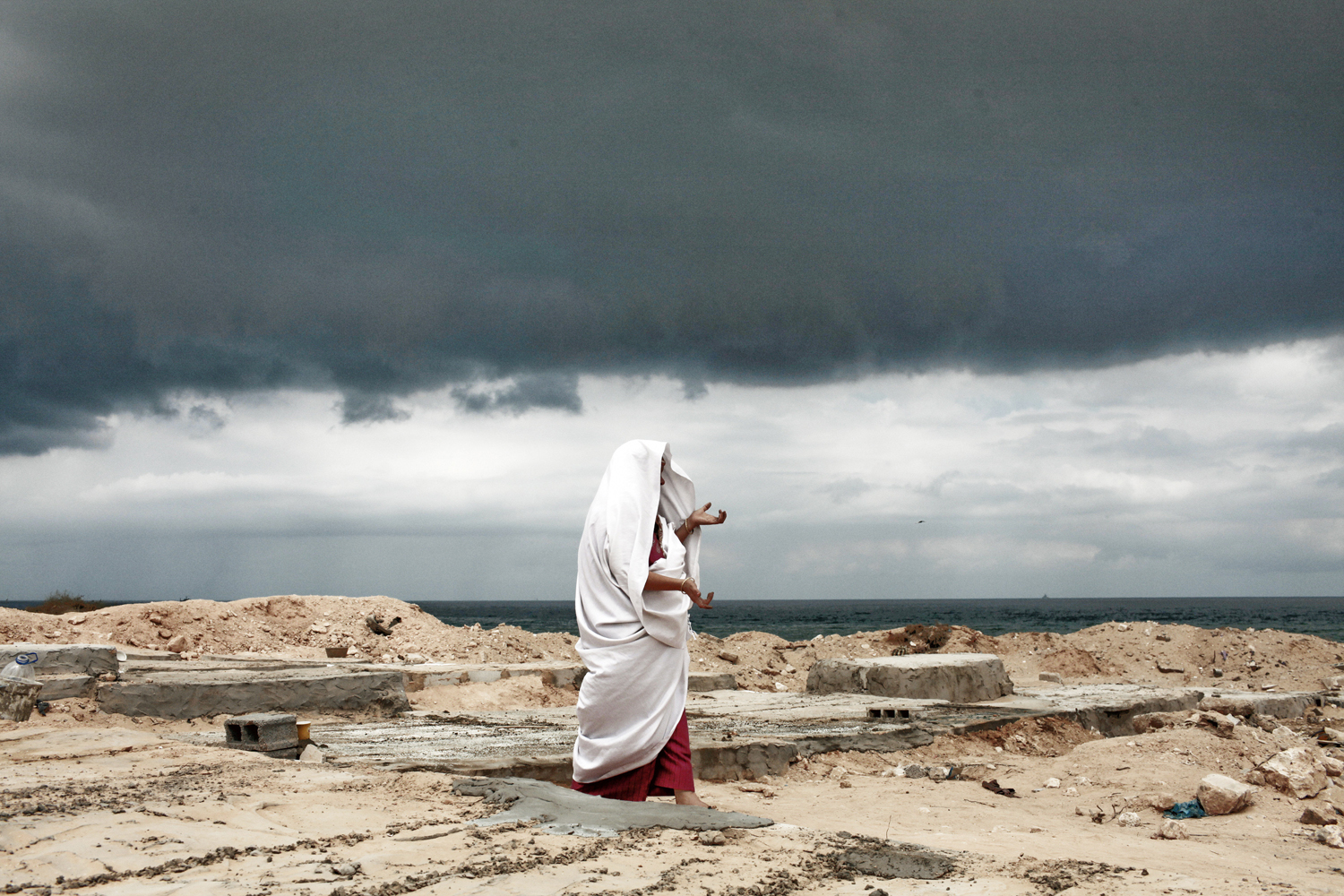September 9, 2011. Under an ominous sky, Eyadea Elspaie visits the gravesite of his son, Tareq Elspaie, who was killed by Gafhafi loyalists last month, at a cemetery in Tripoli. Libyan rebels launched attacks on the loyalist holdouts of Bani Walid and Surt, and Interpol issued an arrest warrant for Col. Moammar Gadhafi.