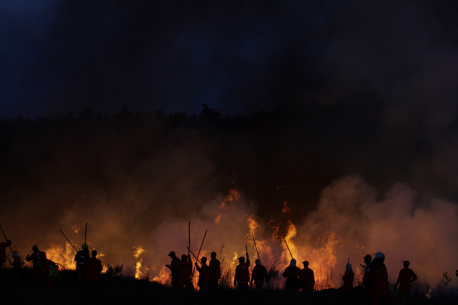 September 9, 2011. Firefighters put out a blaze at a national forest reserve in Brasilia, Brazil. Drought, high temperatures and low humidity have caused fires to start at several places throughout the city.