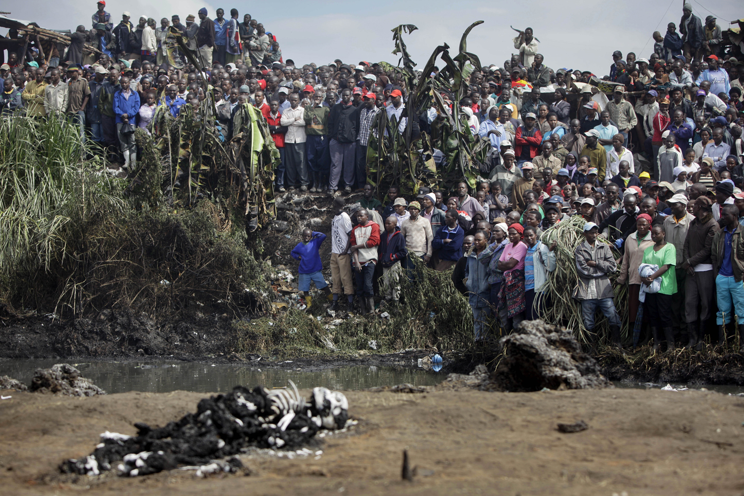 September 12, 2011. Residents of the area look on from across a small river at bodies of victims lying on the other side, after a pipeline explosion in Nairobi, Kenya. A leaking gasoline pipeline in Kenya's capital exploded turning part of a slum into an inferno in which scores of people were killed and more than 100 injuried.