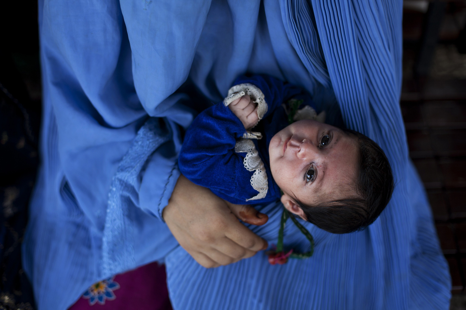 September 11, 2011. An Afghan woman holds her her 11-day-old daughter as they await to go back to Afghanistan from a United Nations funded repatriation centre in the western city of Peshawar. About 3.5 million Afghans have returned home since 2002 from Pakistan with the assistance of aid agencies.