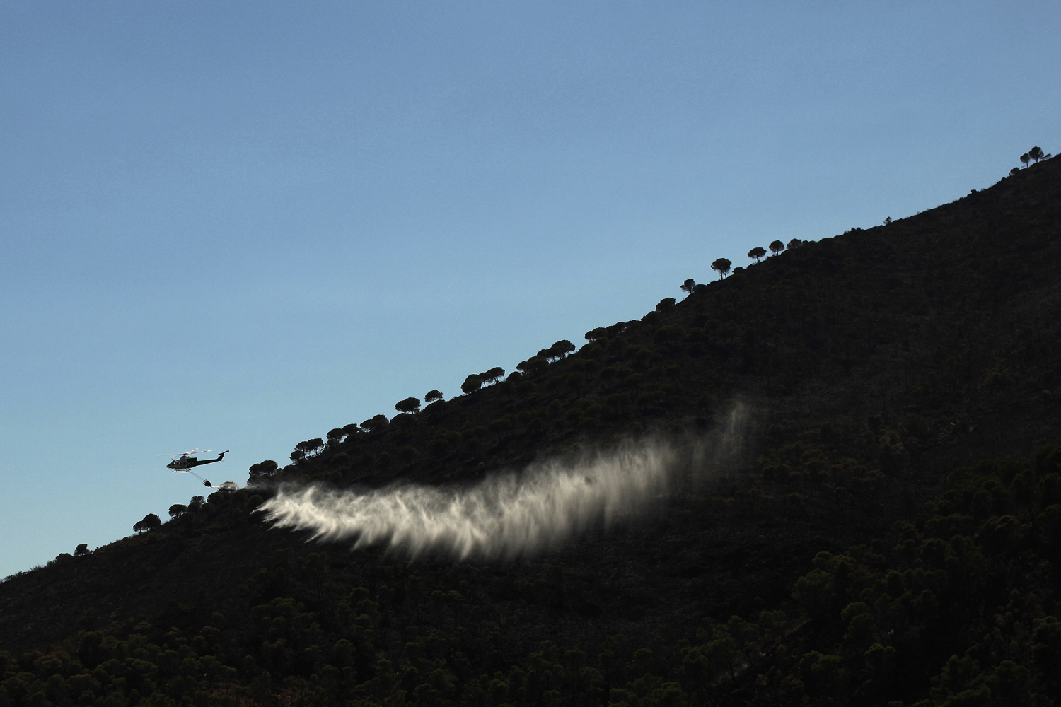 September 12, 2011. A helicopter drops water over a wildfire in the neighborhood of Entrerrios in Mijas, near Malaga, Spain.