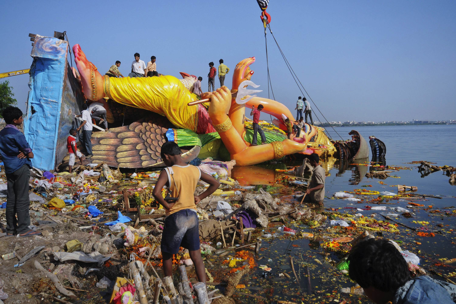 September 12, 2011. Boys climb atop the Hindu elephant god Ganesh, the deity of prosperity, after it was immersed in the waters of Tank Bund Lake to mark the end of Ganesh Chaturthi festival in the southern Indian city of Hyderabad. Ganesh Chaturthi is a ten-day long Hindu religious festival which ends with the immersion of the idols that are taken through the streets in processions, accompanied by dancing and singing, to water tanks, lakes, rivers or seas. The immersion not only symbolizes a ritual send-off to the deity on his journey to his heavenly abode but also carrying away of the misfortunes of mankind.