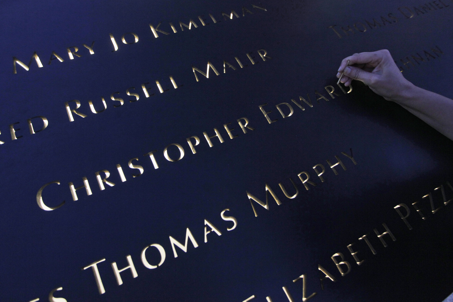 September 11, 2011. Christine Corday puts final touches on the name panels on the north pool at the National September 11 Memorial before a ceremony marking the 10th anniversary of the attacks at the World Trade Center site in New York.