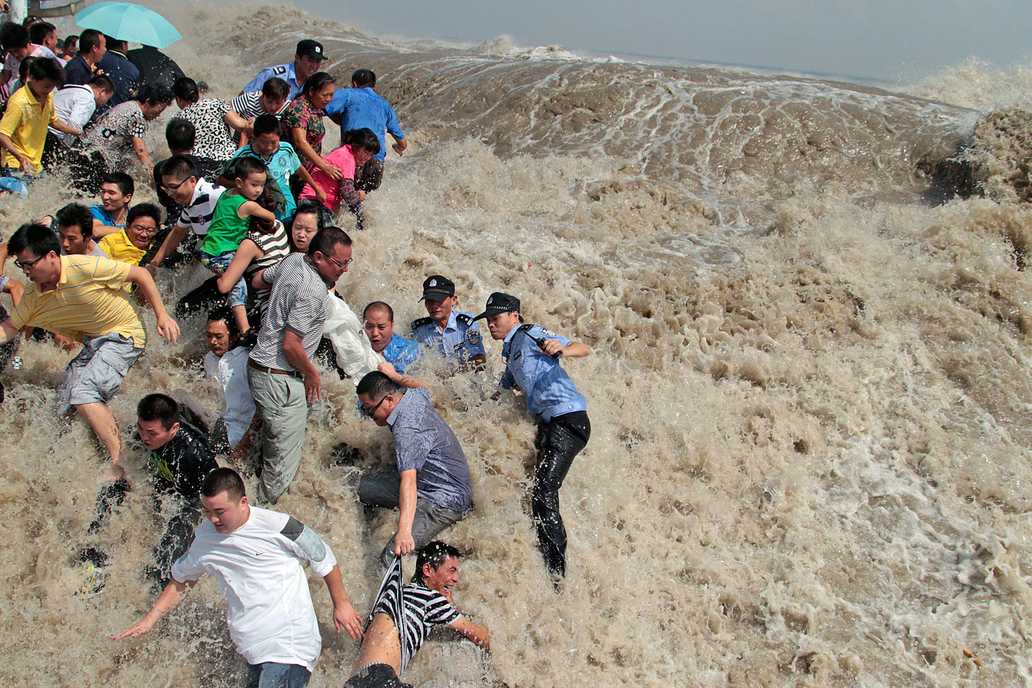 August 31, 2011. Policemen and residents run as waves from a tidal bore surge past a barrier on the banks of Qiantang River in Haining, Zhejiang province. As Typhoon Nanmadol approaches eastern China, the tides and waves in Qiantang River recorded its highest level in 10 years.