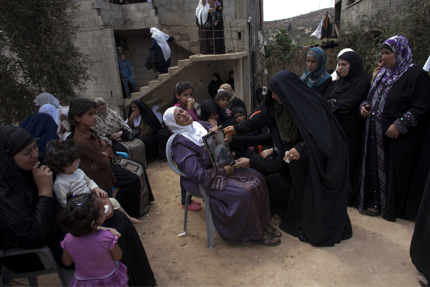 September 24, 2011. Palestinian woman Lafata Achemed Bedran, the mother of Issam Bedran, is comforted by a relative as family members and friends mourn at the funeral of her son in the West Bank village of Qusra. Issam was shot dead during clashes with Israeli soldiers just before Mahmoud Abbas was about to give his speech at the United Nations where he submitted a letter asking for full UN membership.