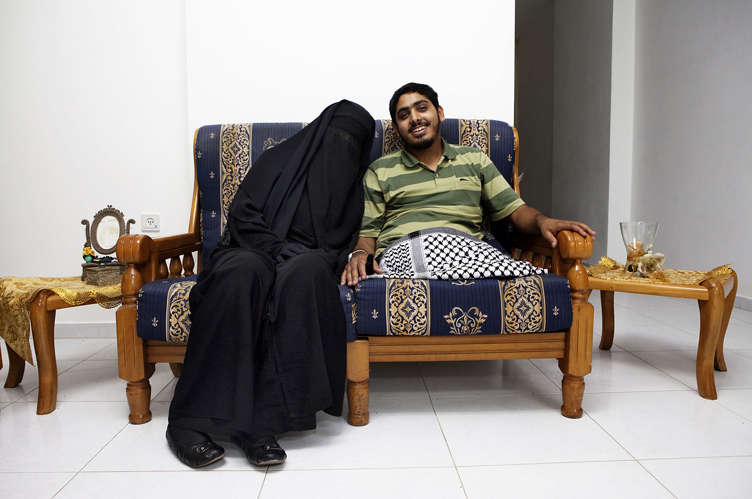 Deema Aydieh, 20, and Moemen Faiz, 21, sit together at their home donated by an Islamic charity in Saudia Arabia. Aydieh, a photographer, lost both his legs during an Israeli attack of Gaza in 2008.