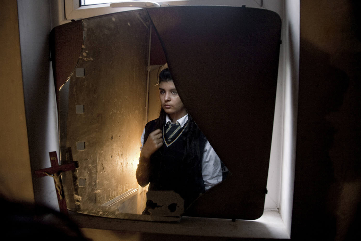 A teenage schoolgirl seen in her home, which is full with Catholic and Islamic items. Her Irish Catholic Mother and Bengali Muslim father have influenced her to practice both religions at different points in her life.
