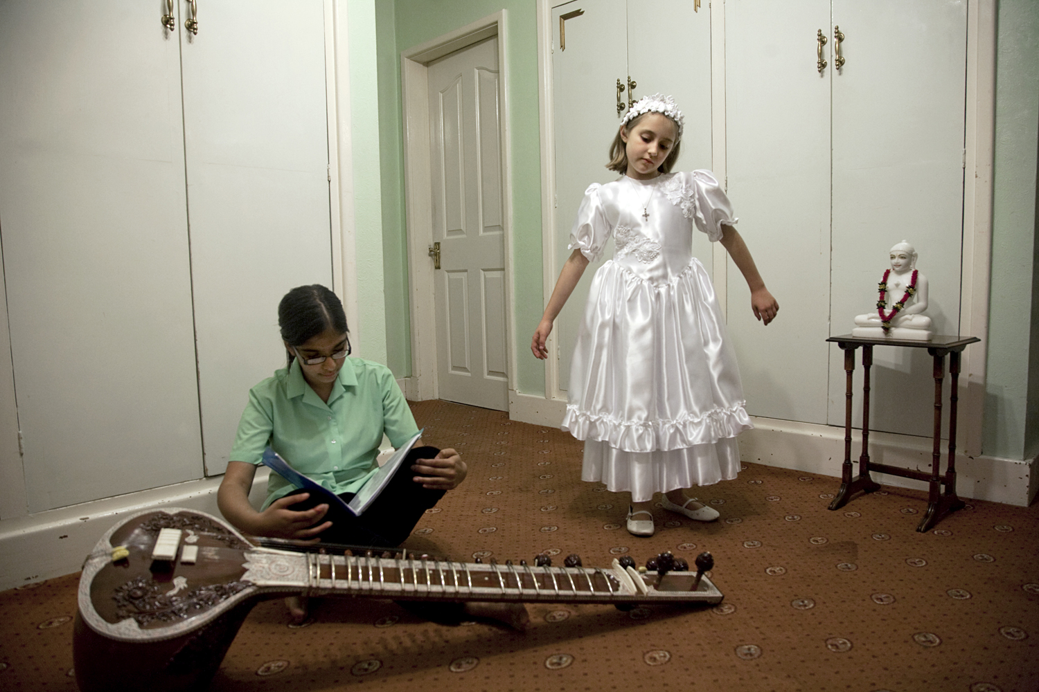 Two young girls from different religious backgrounds play together. The Jain girl takes Indian Sitar lessons in her British school.