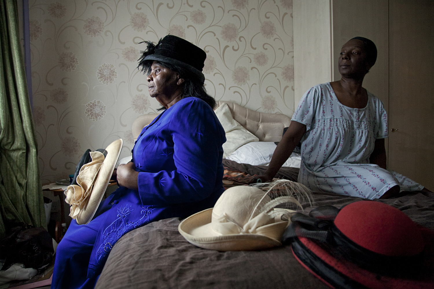Jamaican-born Mrs. Adina Clarke and her daughter review her hat collection before church. In Jamaican tradition Adina keeps a separate part of her wardrobe for her Sunday clothes and refrains from wearing them for any occasion other than church.