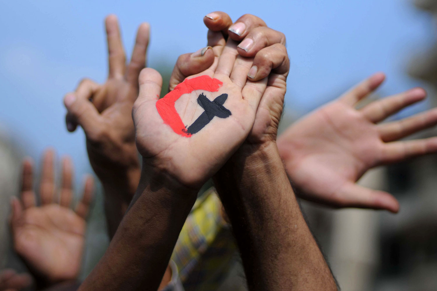 October 14, 2011. A cross and a crescent are painted on the palm of an Egyptian demonstrator holding the hand of a fellow protester during a rally in support of national unity in Cairo's Tahrir Square, days after 25 people, mostly Coptic Christians, were killed in weekend clashes with Egyptian security forces.
