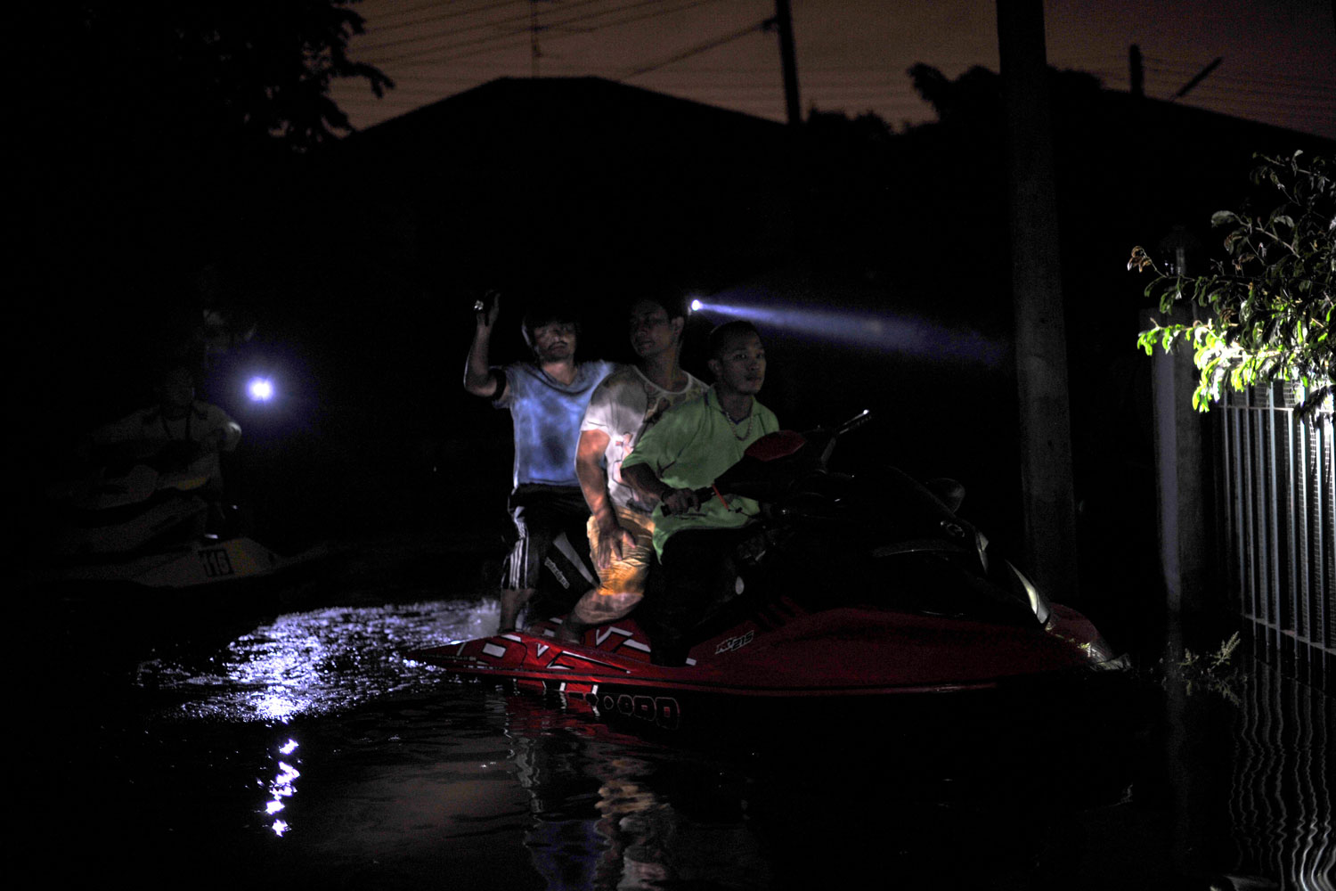 October 15, 2011. Highway police and motorway jetski club volunteers patrolled and handed out food and water to stranded residents along a flooded street in Pathum Thani province in suburban Bangkok. Thousands of sandbags piled alongside a canal on the northern edge of Bangkok form the last line of defense between the city of 12 million people and a wall of floodwater bearing down on the capital.