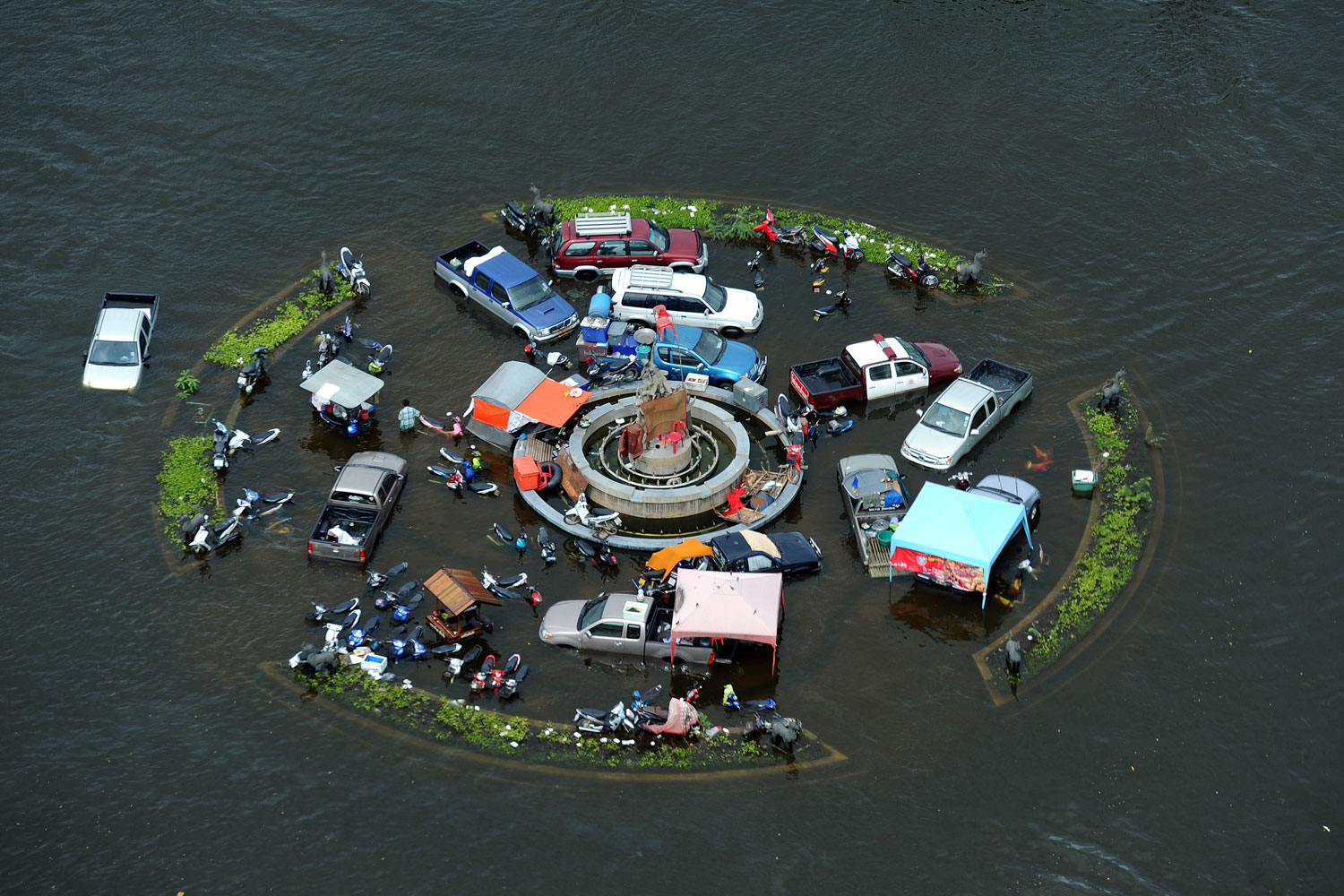 October 16, 2011. In Thailand's ancient capital city of Ayutthaya, a circle of vehicles sit partially submerged in floodwater. Inland flooding that encroached on the modern capital, Bangkok, has claimed 300 lives and displaced tens of thousands.