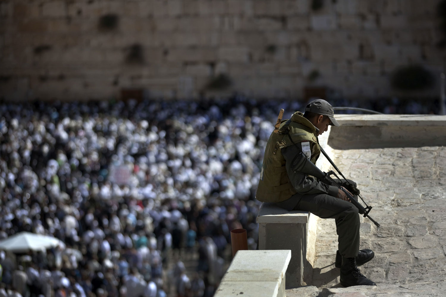 October 16, 2011. An Israeli border guard secures the areas as thousands of Jewish men and women participate in a mass Cohanim prayer (priest's blessing) during the annual pilgrimage festival of Sukkot, or the feast of the Tabernacles, at the Western Wall in Jerusalem's Old City. Thousands of Jews make the week-long pilgrimage to Jerusalem during the holiday which commemorates the desert wanderings of the Israelites after their exodus from Egypt.