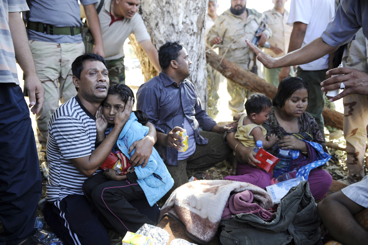October 17, 2011. Libyan National Transitional Council (NTC) fighters provide displaced Bangladeshis with food and drink after fleeing Sirt during heavy fighting between loyalist troops and NTC forces. Families of former Libyan regime officials streamed out of the coastal city, including the mother and brother of Muammar Gaddafi's spokesman Mussa Ibrahim.