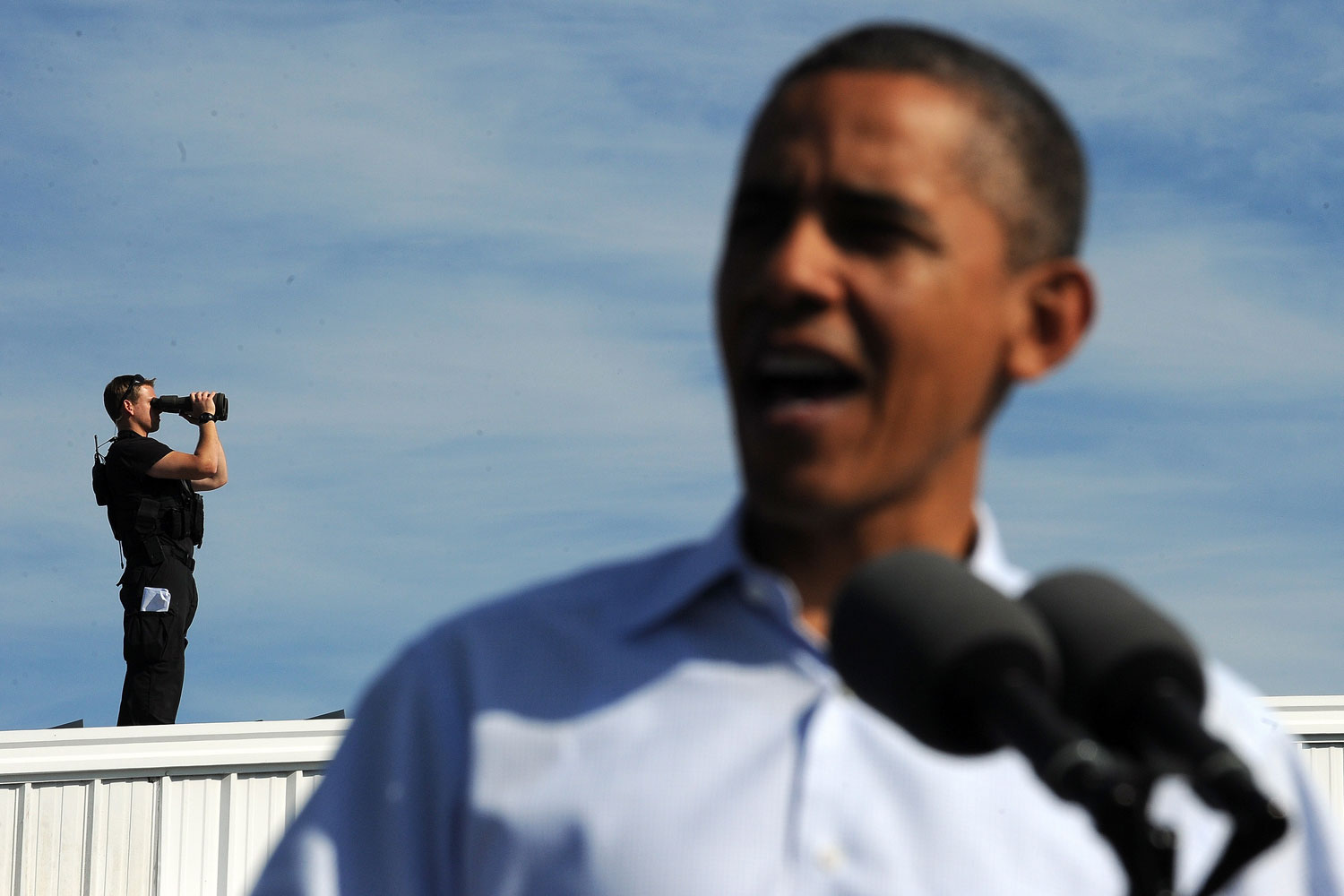 October 17, 2011. An agent scans the area from a rooftop as President Barack Obama speaks at the Asheville Regional Airport in Fletcher, North Carolina, during the first day of his three-day American Jobs Act bus tour to discuss jobs and the economy.