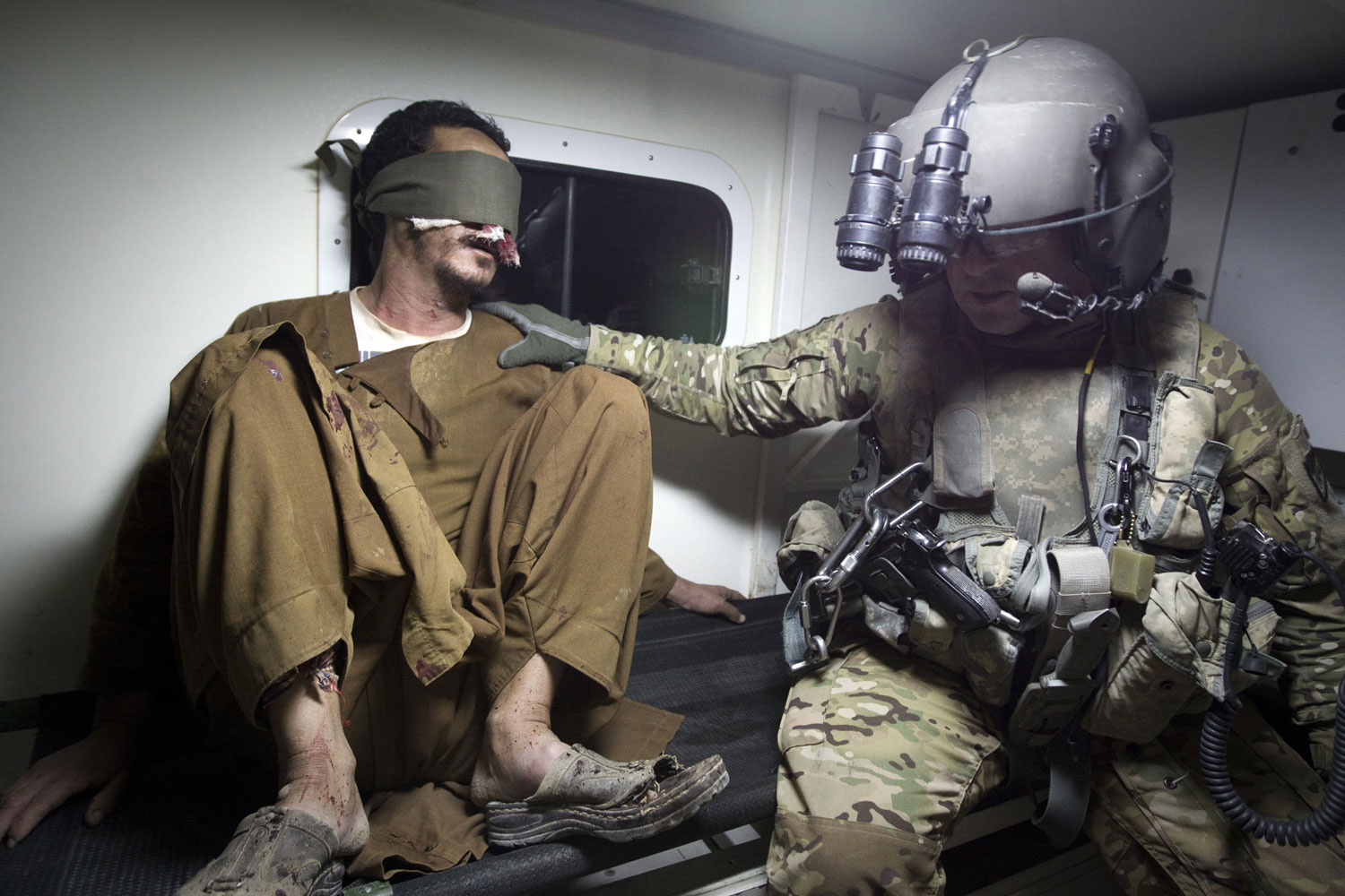October 17, 2011. US Flight Medic, sergeant 1st class Joseph Lemons (R) from 159th Brigade Task Force Thunder comforts the blindfold Afghan civilian cook, Salman Gowhar in an ambulance on the way to the Kandahar Hospital Hero after airlifting him from the Khakriz village in Kandahar province. Salman was injured by the steam blown on his face and eyes while cooking in his village in Kandahar province.