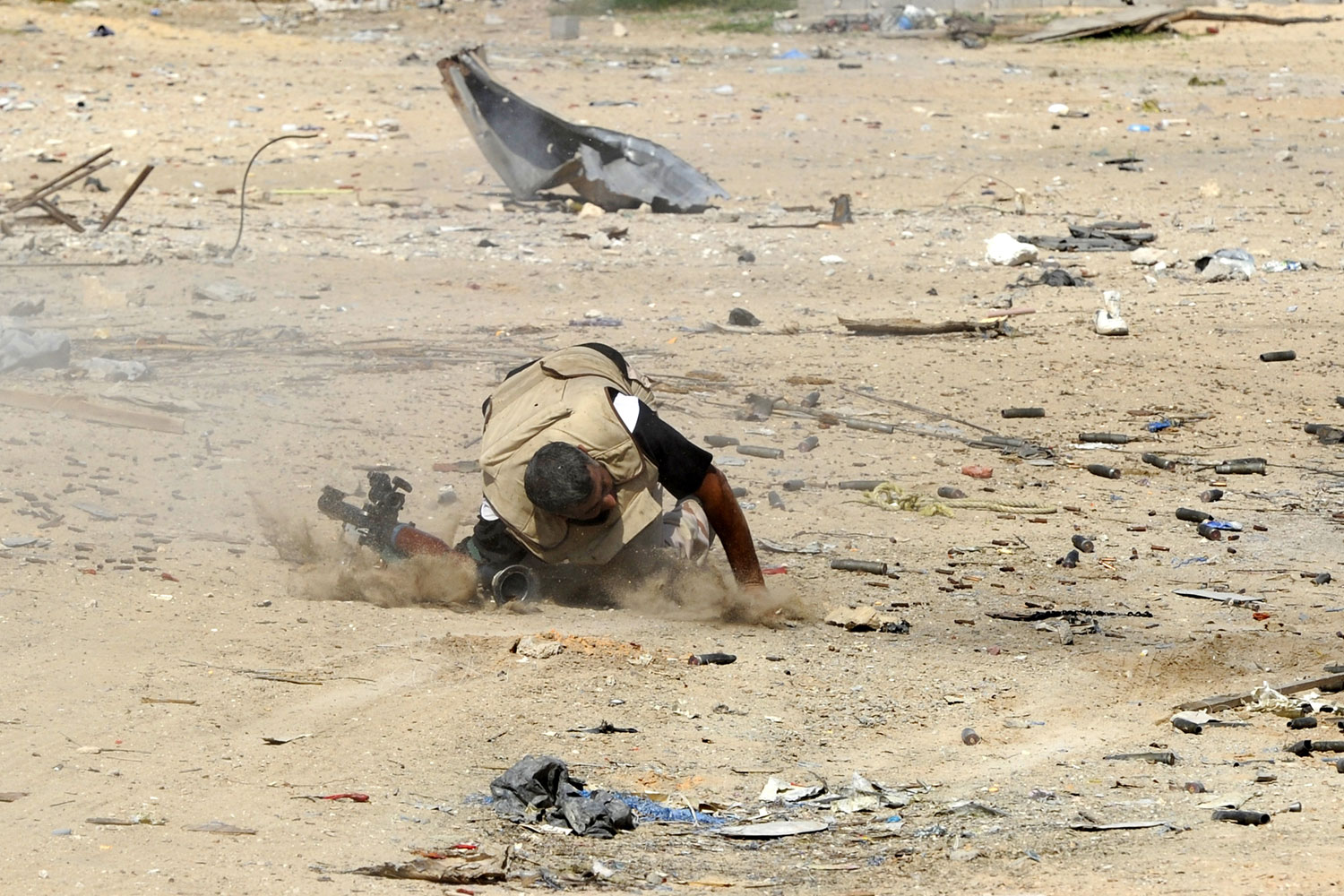 October 18, 2011. A Libyan National Transitional Council (NTC) fighter falls on the ground after being shot during a street battle in Sirt. Fierce street fighting erupted in Muammar Gaddafi's sole remaining bastion of Sirt as streets reverberated with the sound of heavy gunfire, rockets and mortars.