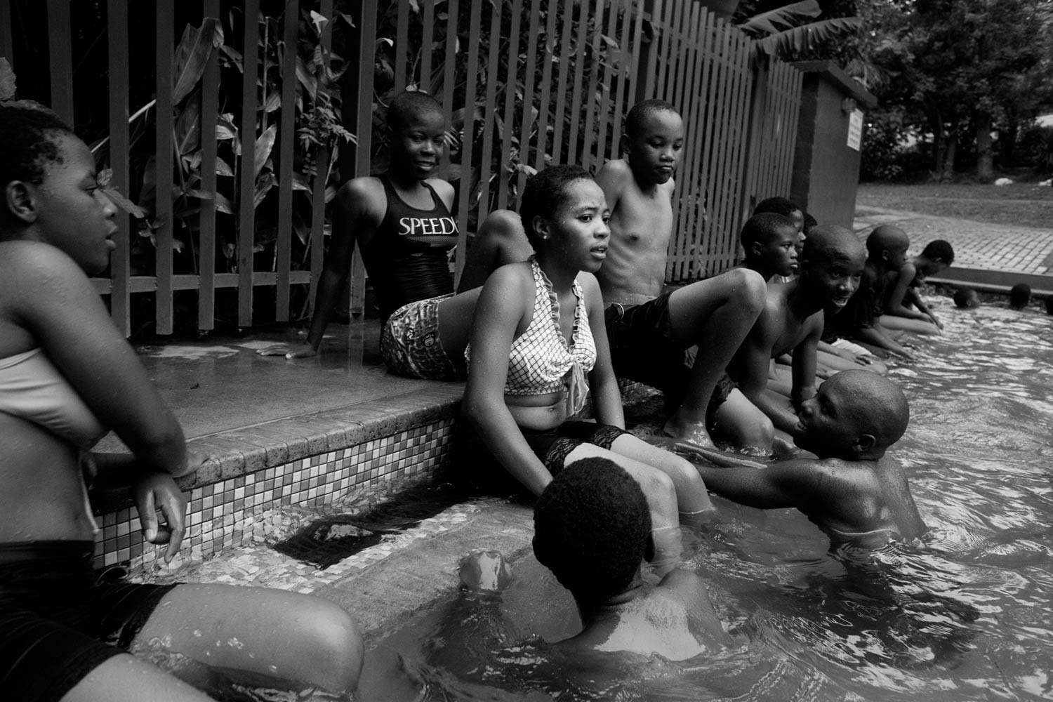 Young men flirt with teenage girls at a local swimming pool.