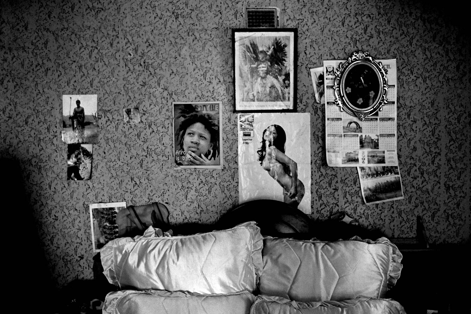 Decorations hang on the wall behind a young girl's bed that she shares with her mother in a one-room home.