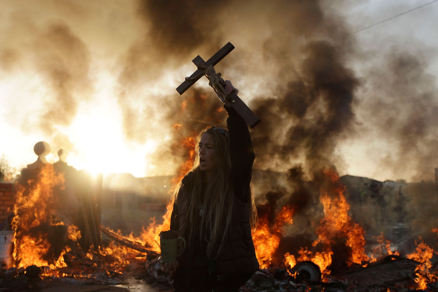 October 19, 2011. An Irish traveler resident holds up a cross for the media, in front of a burning barricade during evictions at the Dale Farm travelers site, near Basildon England, 30 miles east of London. Police in riot gear used sledgehammers to clear the way for the eviction of a community of Irish travelers from a site where they have lived illegally for a decade.