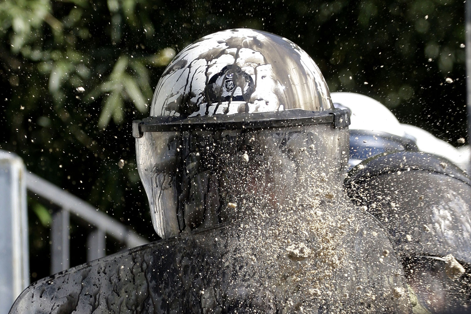 October 19, 2011. A piece of plaster torn from a building and thrown by a protester shatters as it hits the paint-spattered helmet of a riot policeman, during clashes in central Athens. Greek anger over new austerity measures and layoffs erupted into violence, as demonstrators hurled chunks of marble and gasoline bombs and riot police responded with tear gas and stun grenades that echoed across Athens' main square.