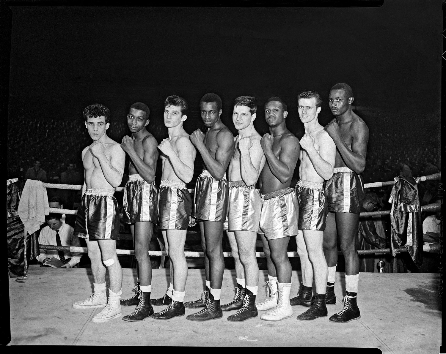Boxers, possibly Golden Gloves contenders, line up in a boxing ring, 1955.