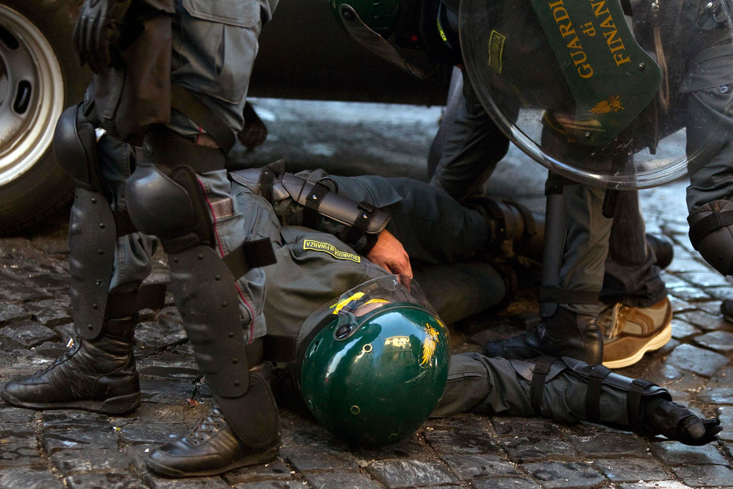 October 15, 2011. A tax police officer is helped by colleagues as he lies on the ground during clashes in Rome. Italian police fired tear gas and water cannons as protesters in Rome turned a demonstration against corporate greed into a riot, smashing shop and bank windows, torching cars and hurling bottles. The protest in the Italian capital was part of  Occupy Wall Street  demonstrations against capitalism and austerity measures that went global, leading to dozens of marches and protests worldwide.