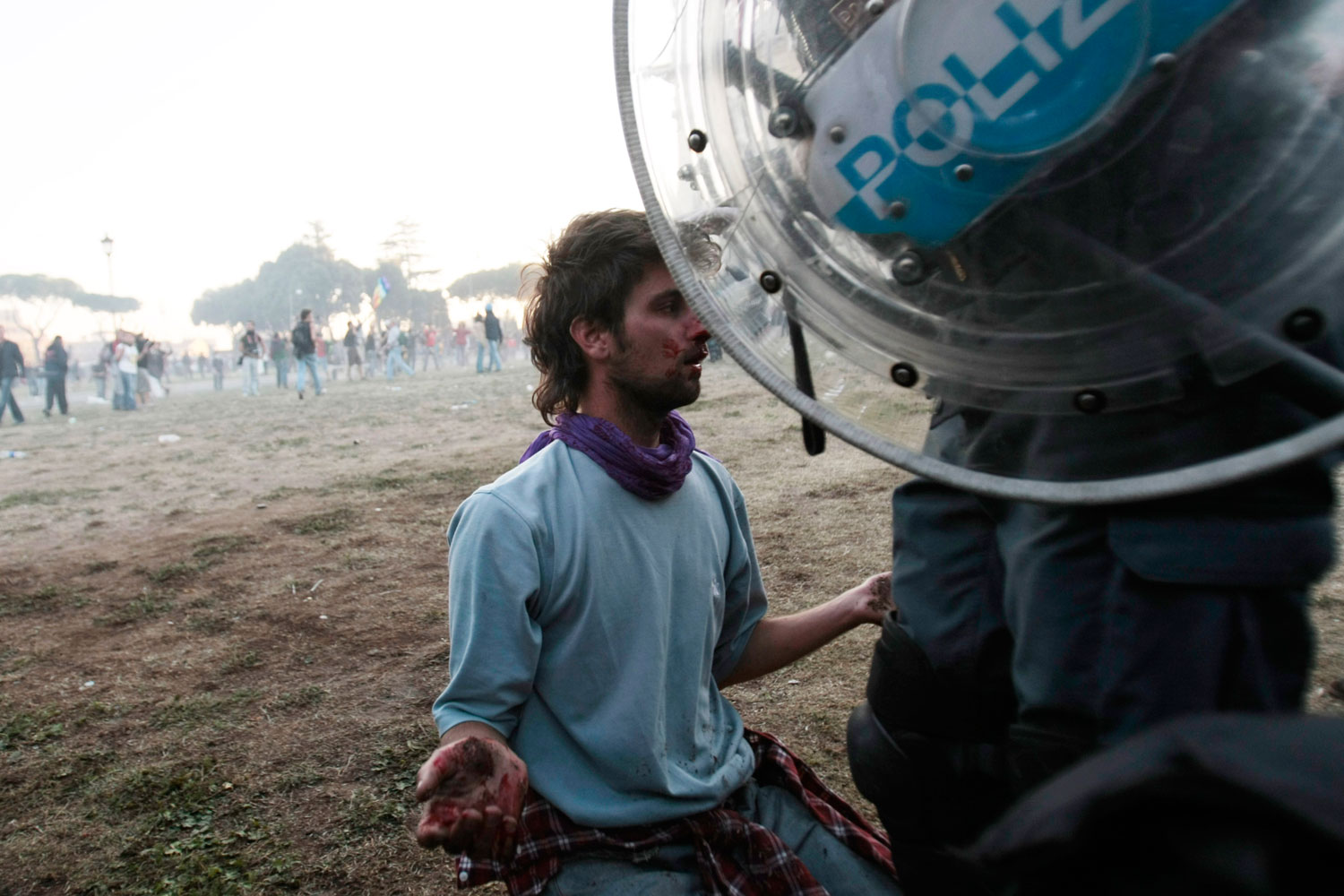 October 15, 2011. An injured Occupy Wall Street protester kneels before a police officer in Rome. Protests against banks, wealth inequality and economic policies have spread to dozens of cities worldwide. In Rome, police fired tear gas and water cannons as protesters smashed windows, threw bottles and set cars ablaze.