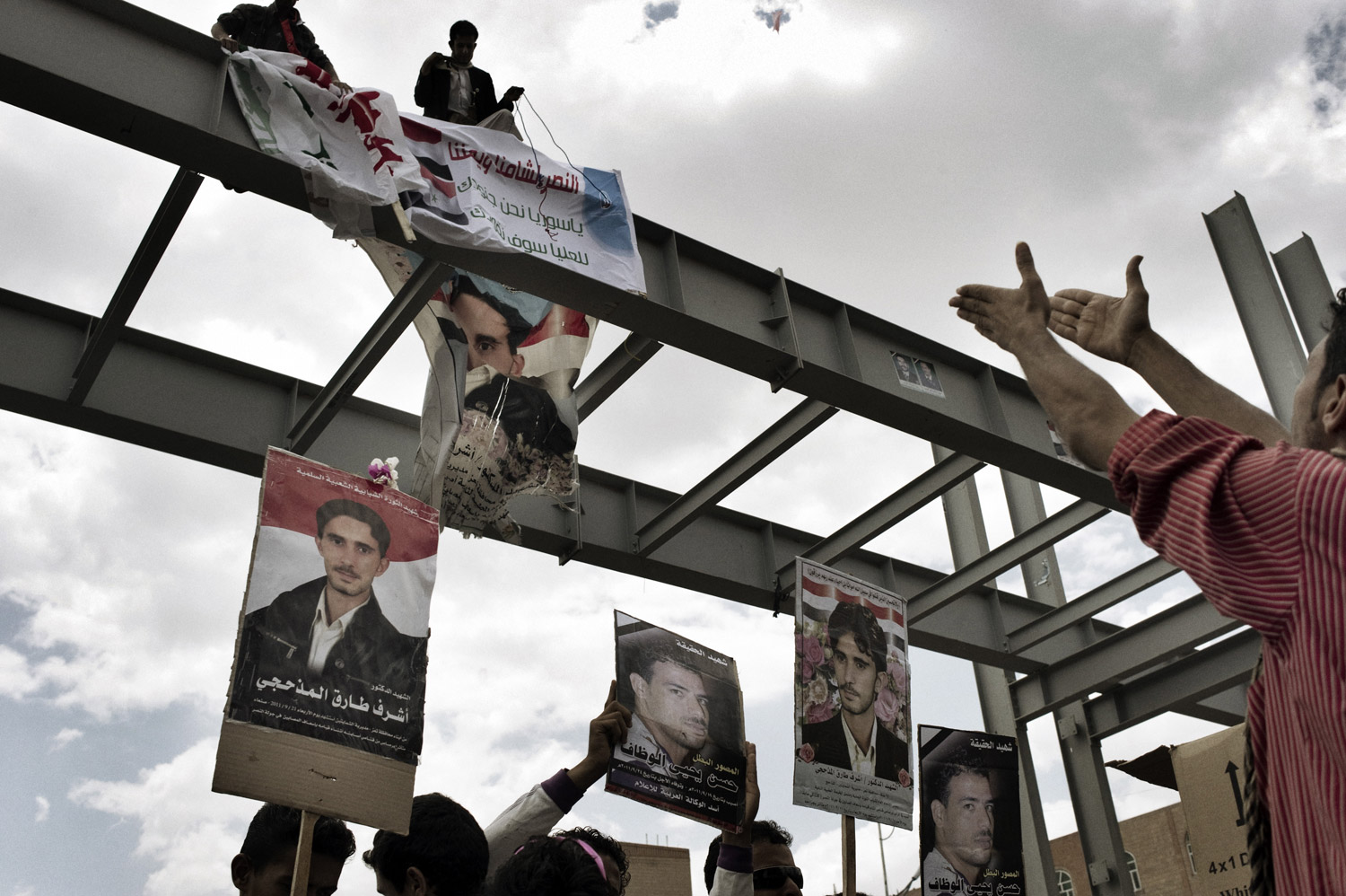 A Yemeni protestor waves posters of demonstrators recently killed during clashes in Syria on September 30, 2011.