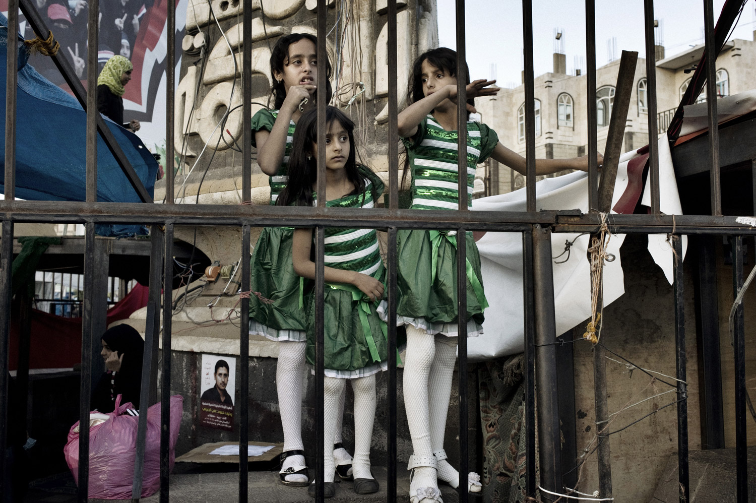 Young girls scramble onto a fence during a protest in Change Square on October 1, 2011.