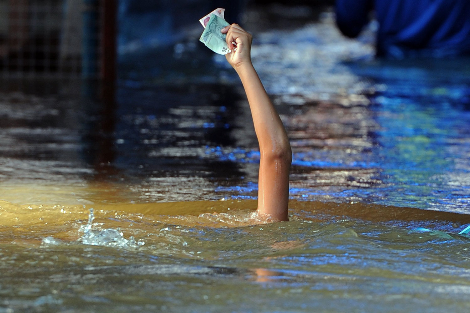 October 15, 2011. A Thai boy holds banknotes aloft to keep them dry while he swims during the flood in Nonthaburi province in suburban Bangkok. Thailand fought to hold back floodwaters flowing towards Bangkok as a spring tide hindered efforts to protect the city of 12 million people from the kingdom's worst inundation in decades.