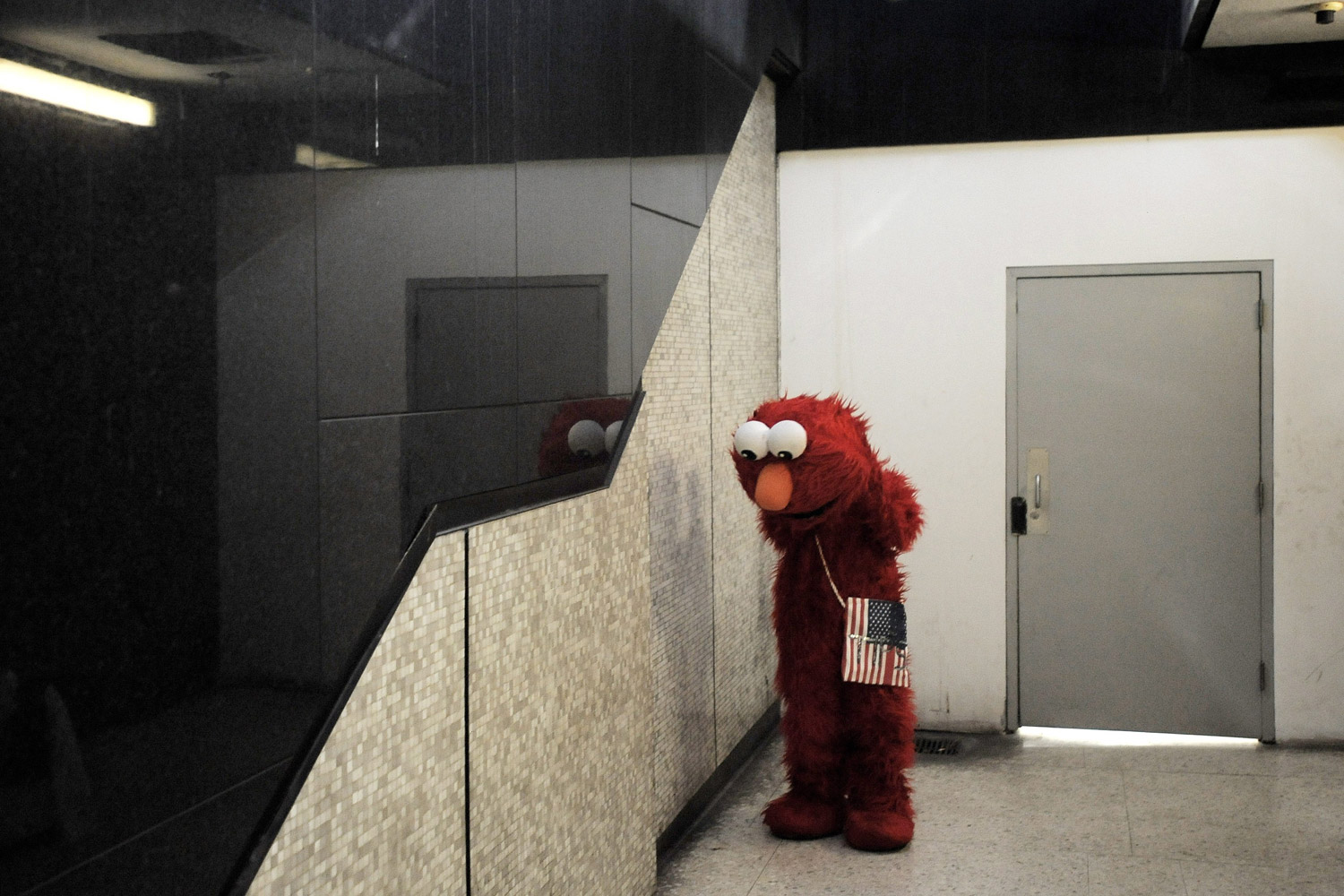 November 18, 2011. A man gets dressed in an Elmo suit to have tourists take his picture near a subway exit in New York.