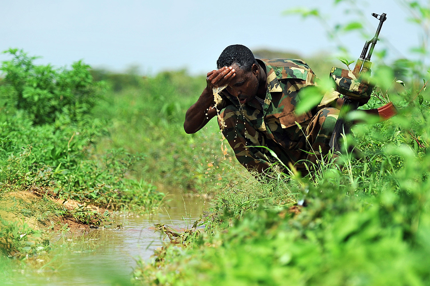 November 21, 2011. A Somali militia washes his face in a lush field near an irrigation scheme that grows onions and vegetables near Dollow, central Somalia. United Nations announced last week that three of six regions of southern Somalia including  Bay, Bakool and Lower Shabelle, that had been declared famine-areas in July were no longer so even though the lives of 250,000 Somalis continue to be threatened by drought.